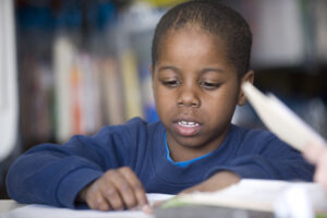 little boy reading in Reading Corps