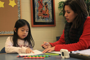 Jenny doing reading interventions with a little girl