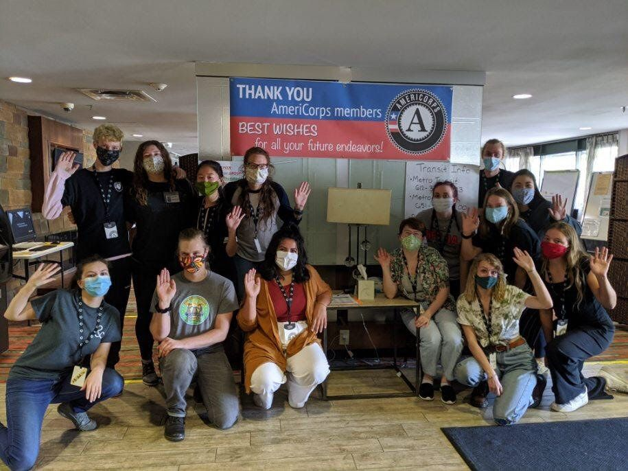 A group of people standing and kneeling around a sign thanking AmeriCorps members